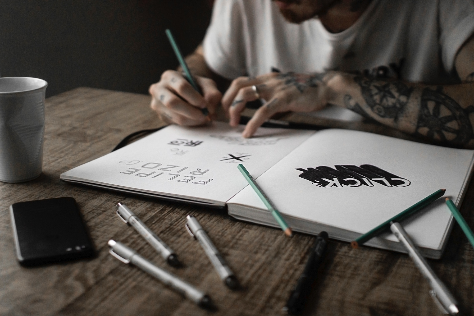 Designer in sketchbook creating typography